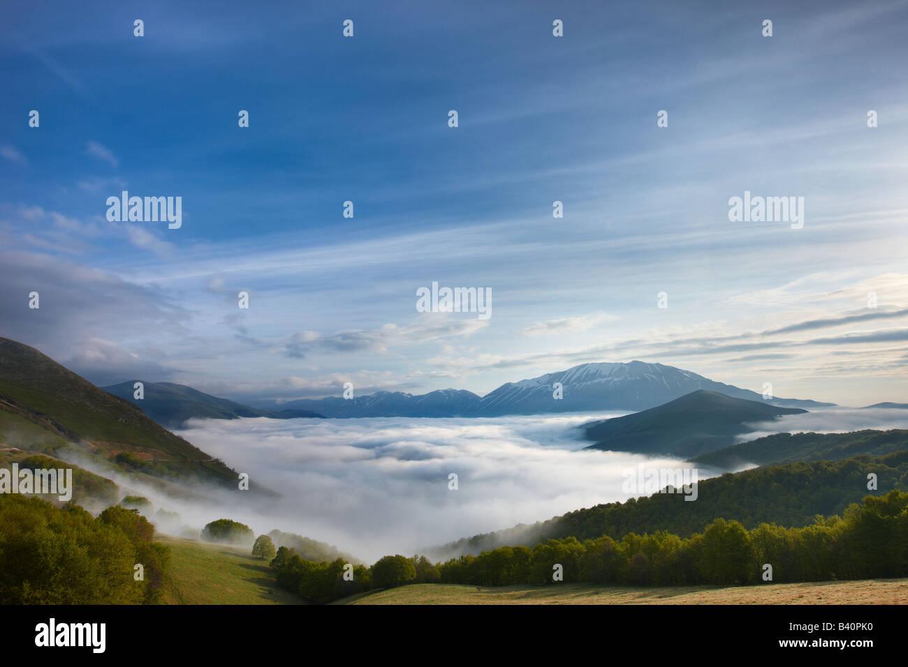 Mist tumbado en el Piano grande al amanecer con las montañas del Parque Nacional de Monti Sibillini elevándose, Imagen De Stock