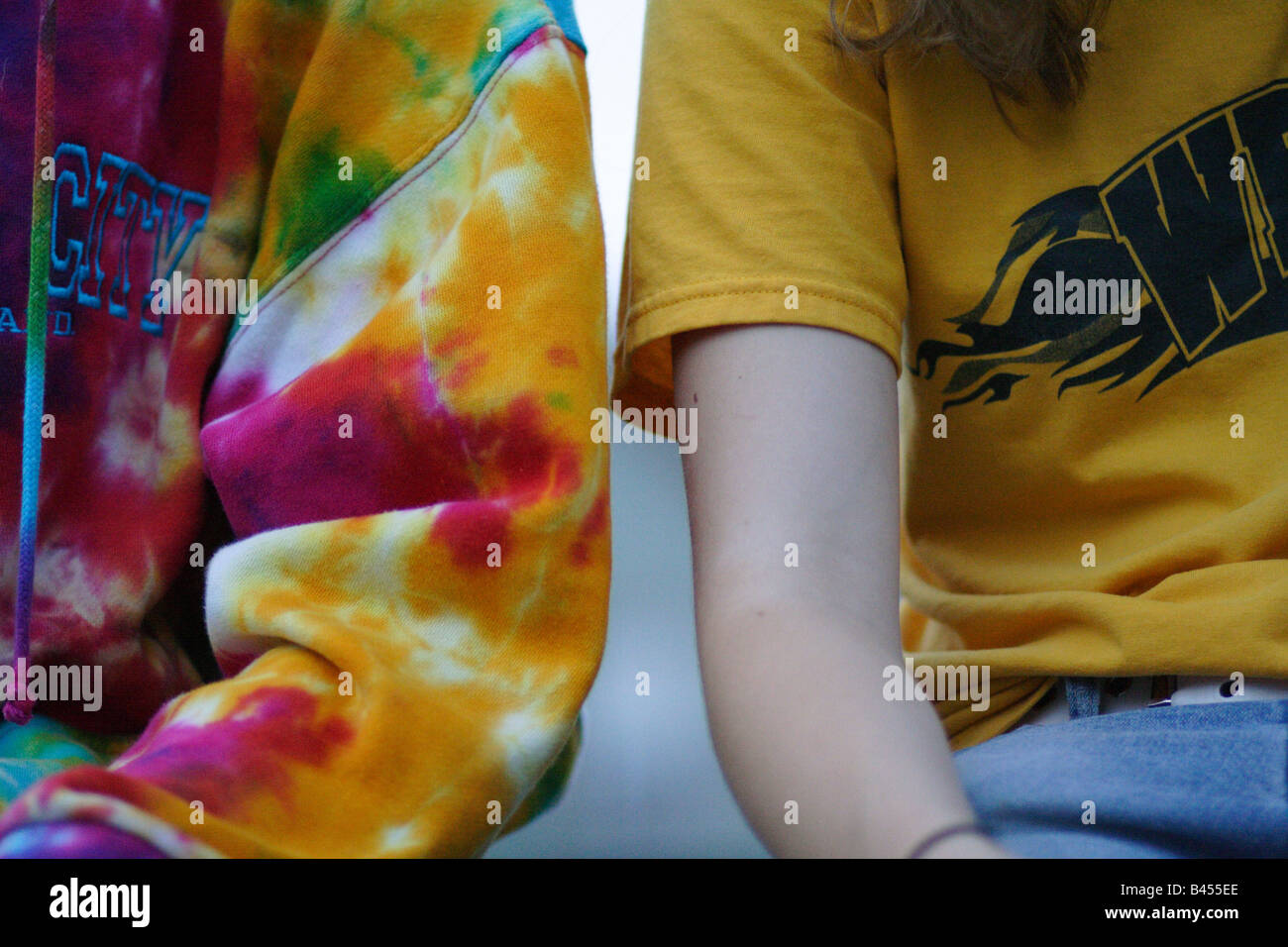Dos personas sentadas una junto a otra en una sudadera y una camiseta de manga corta Imagen De Stock