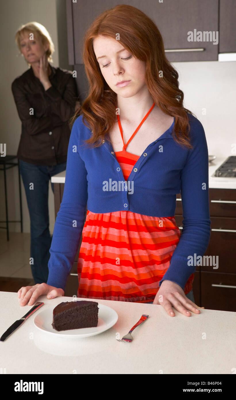 Madre busca a su hija en la cocina con el pastel Foto de stock