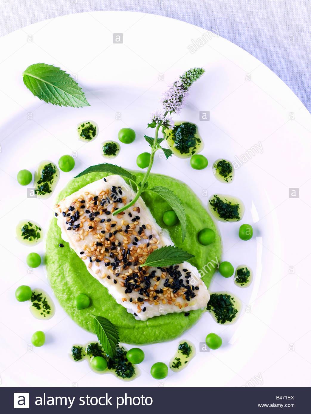 Filete de pescado con sésamo sobre puré de guisantes y vinagreta de limónFoto de stock