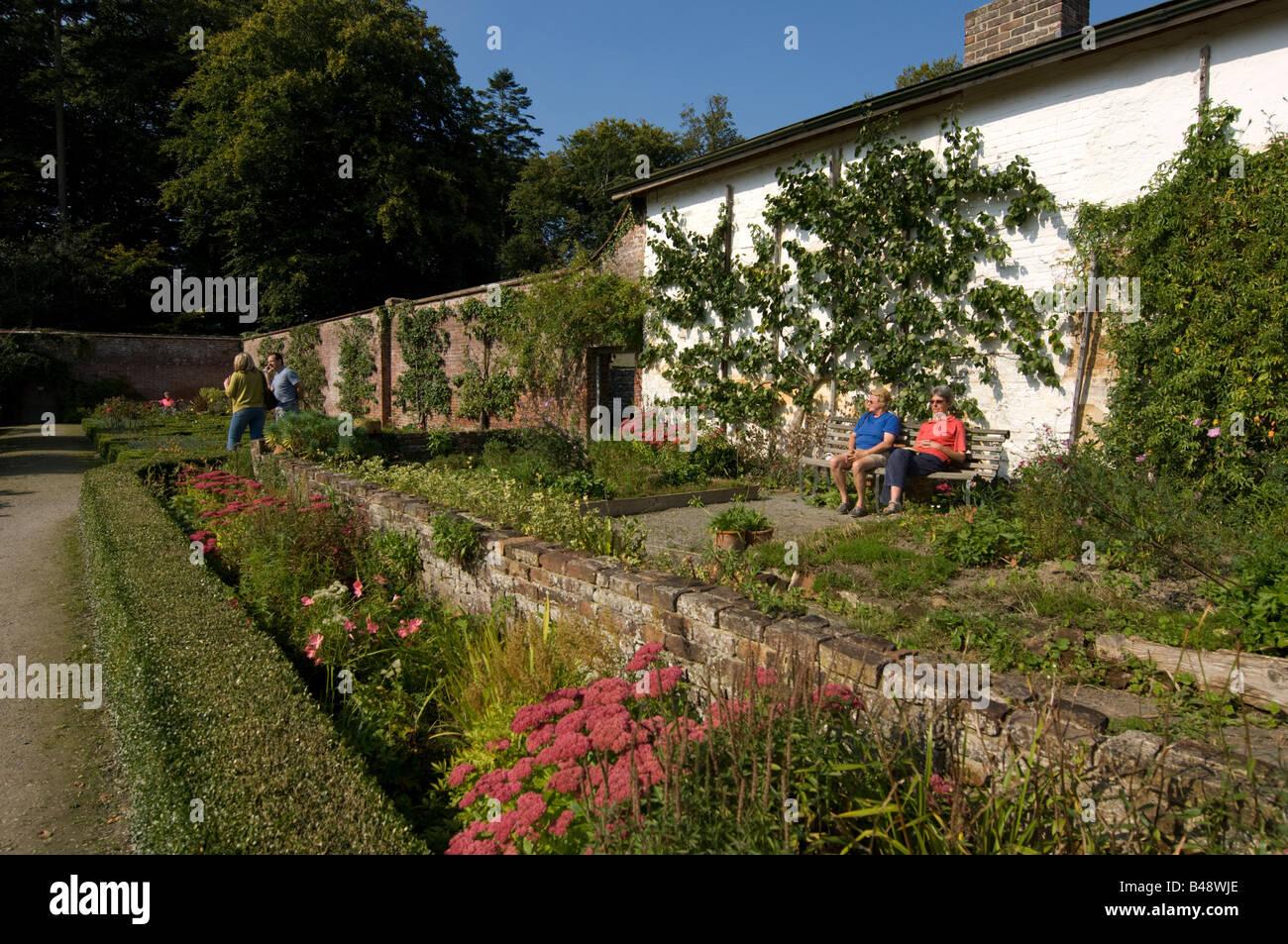 Gente sentada en el recinto amurallado de la huerta de Llanerchaeron Hall Farm y jardines de propiedad de Gales, Foto de stock