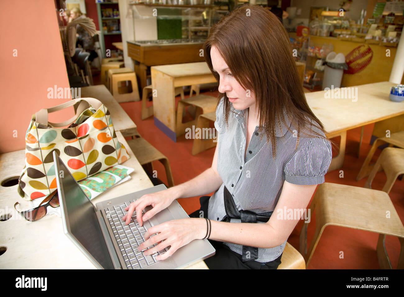 Mujer mediante wifi en el café Bean Shoreditch Londres Imagen De Stock