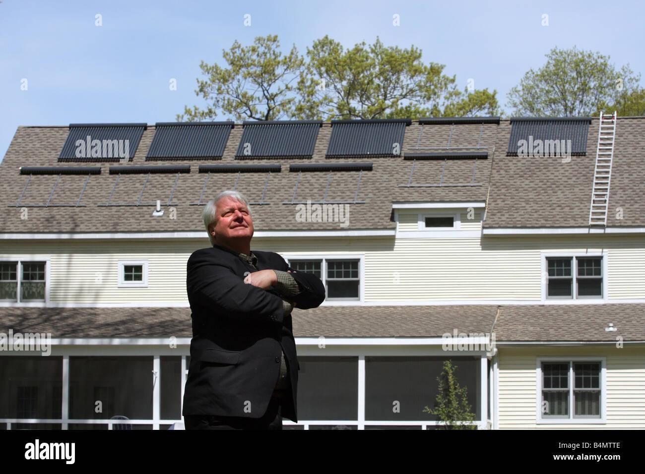 Un hombre con su casa, que dispone de paneles solares en el techo que proporciona energía renovable limpia Imagen De Stock