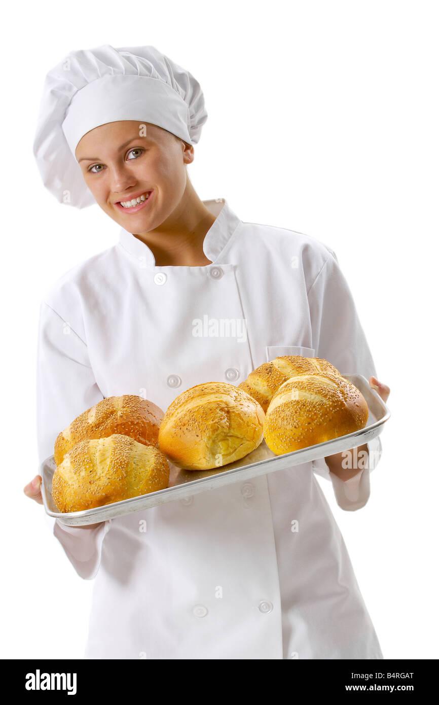 Mujer joven chef sosteniendo una bandeja de pan fresco. Imagen De Stock