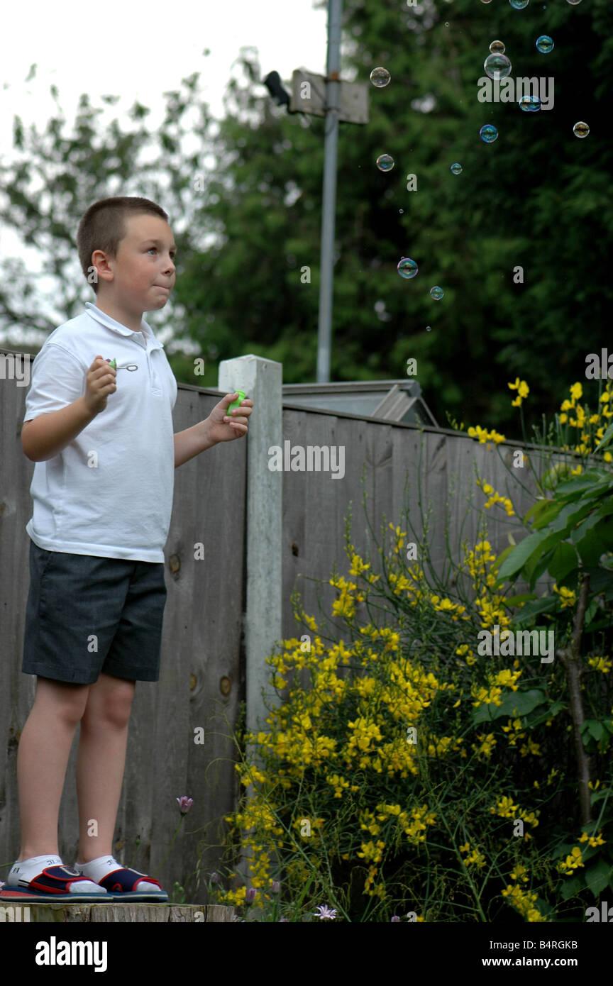 Un muchacho ve el bubles él s apenas soplado lejos de flotación Foto de stock