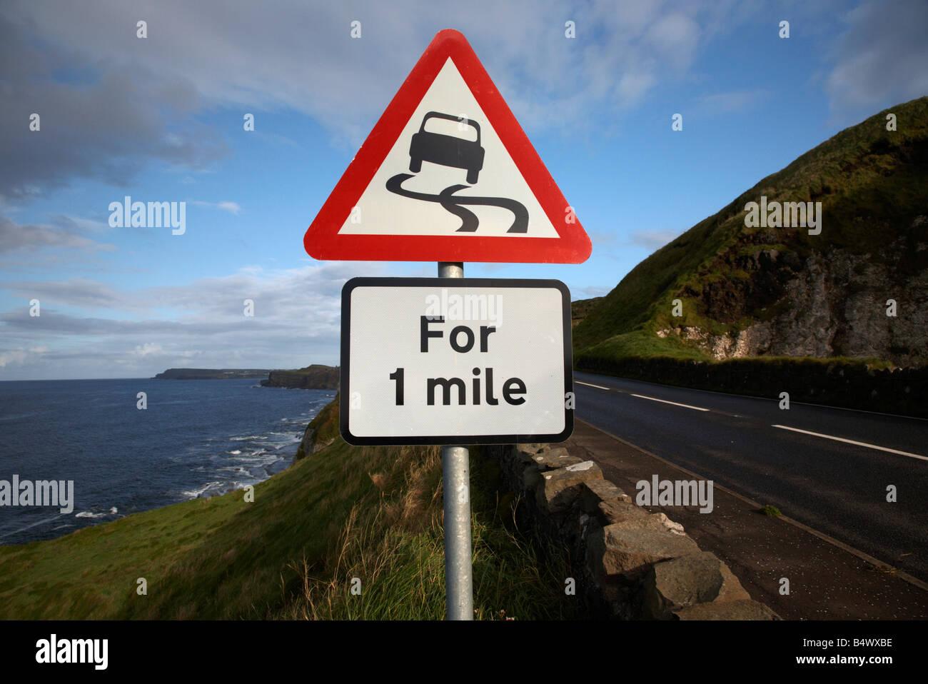 Resbalosa roja de advertencia de peligro el triángulo de 1 milla de firmar en el famoso A2 Norte de Antrim Imagen De Stock