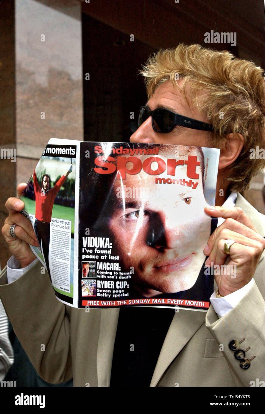 Rod Stewart Septiembre de 2001 sosteniendo un ejemplar de la revista mensual deportiva Sunday Mail Gafas de sol Foto de stock