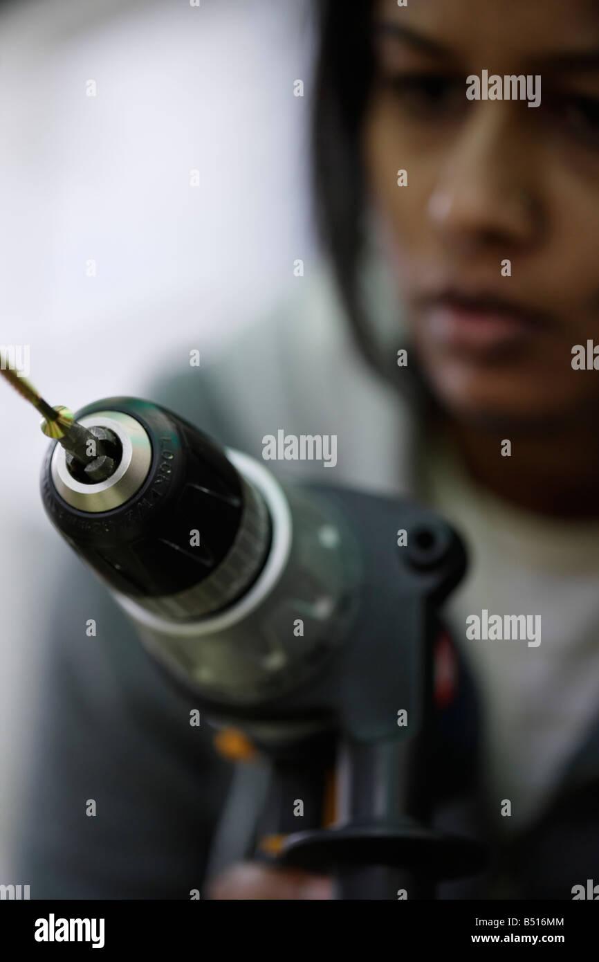 Mujer Asiática usa taladro eléctrico para conducir en un tornillo para madera Foto de stock