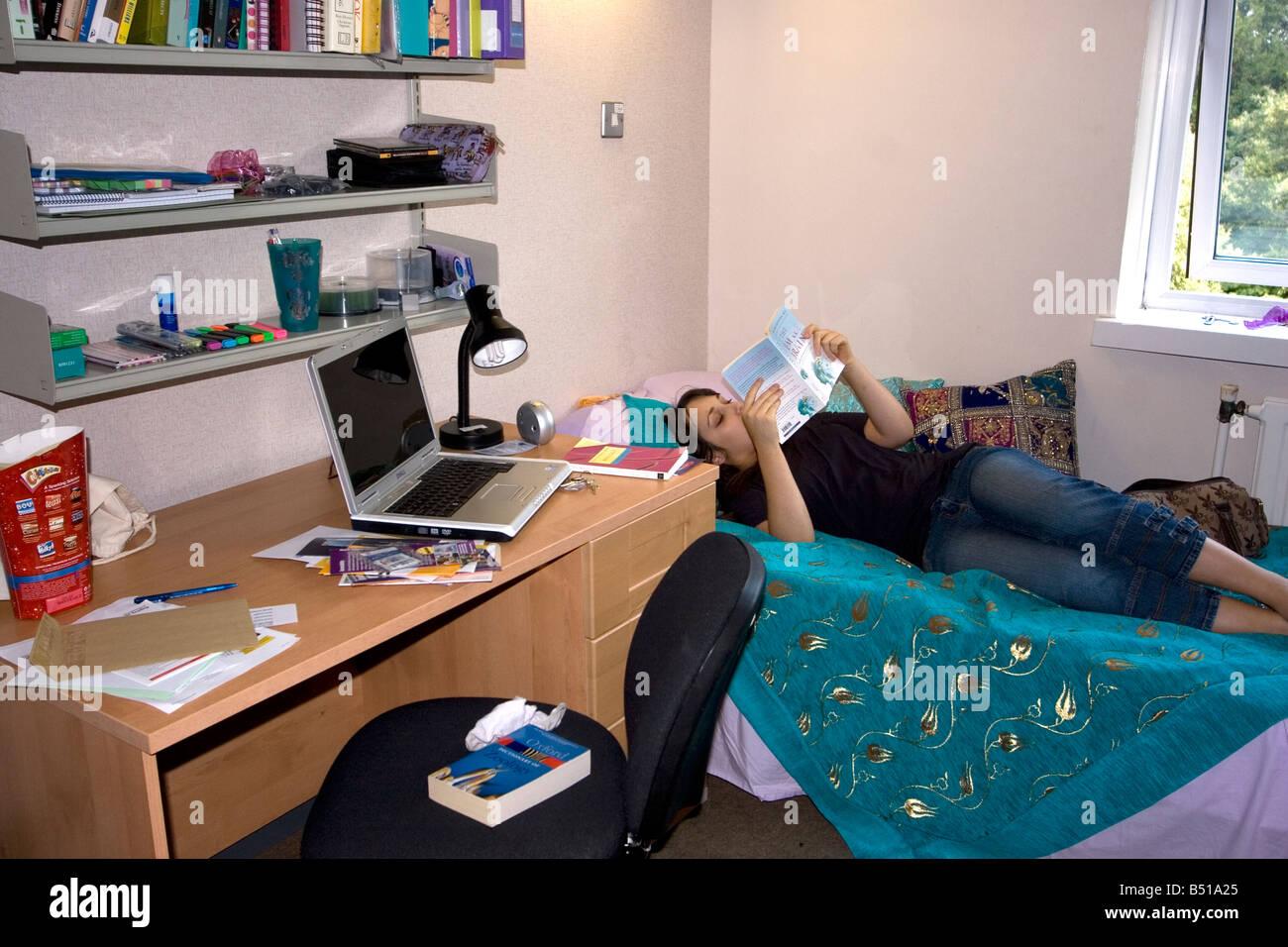 Estudiante de la universidad femenina en su habitación Residencia Universitaria leyendo UK Imagen De Stock