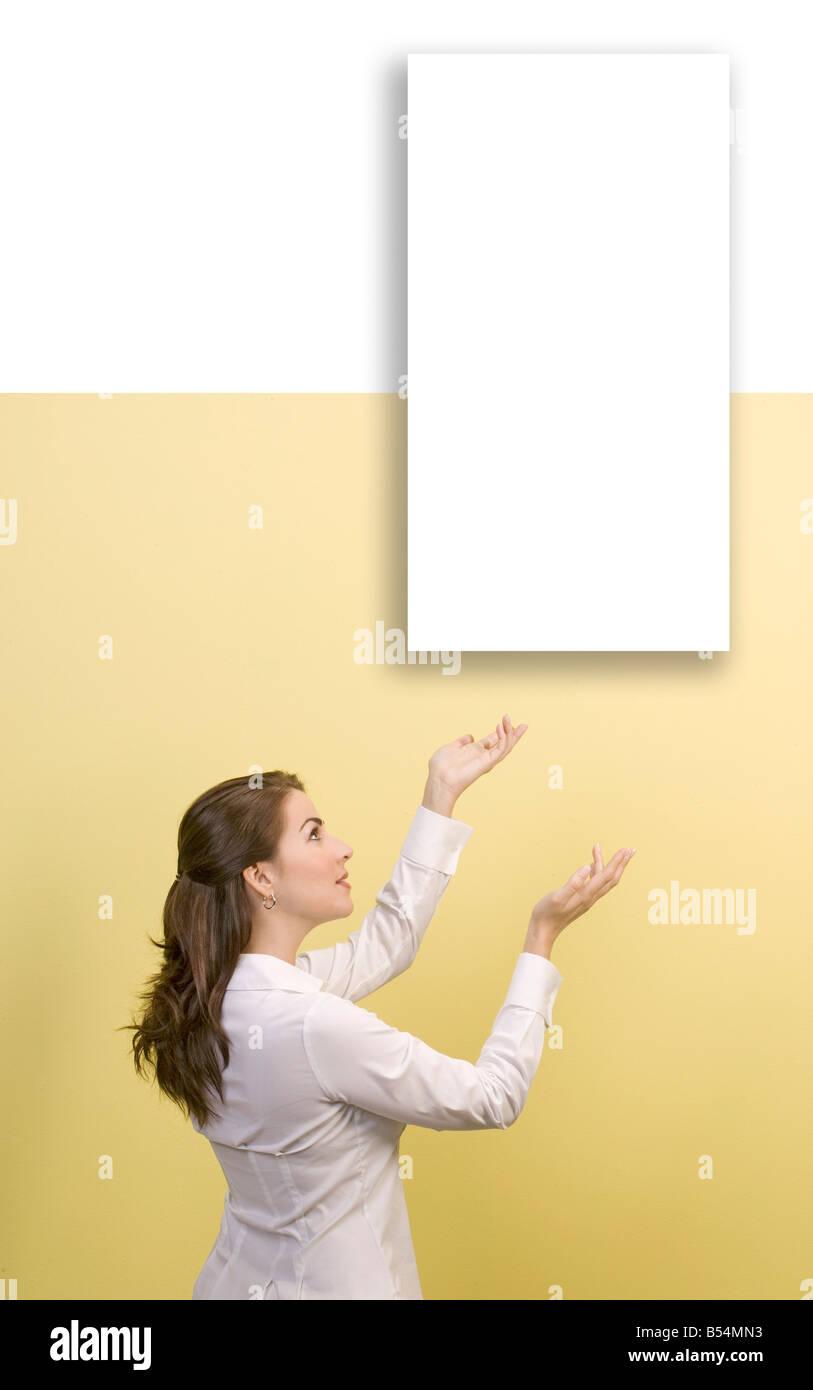 Mujer muestra imagen blanco vacío en la pared Imagen De Stock