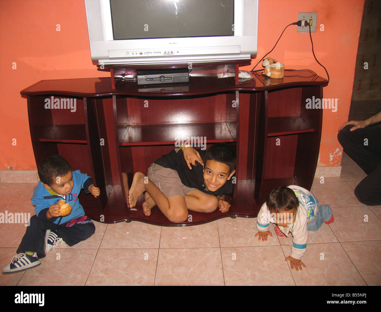 Tres primos feliz (Felipe, Samuel, Gabriel), uno de ellos dentro de un rack de TV, de Sepetiba, Río de Janeiro, Brasil / Brazil Foto de stock