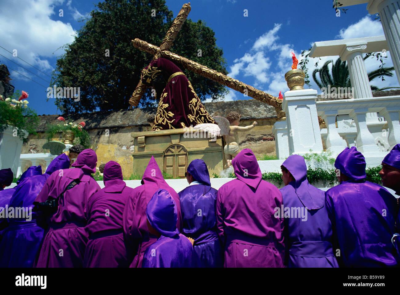 Los hombres en túnicas púrpuras que portan enormes flotan en uno de los famosos desfiles de Semana Santa en Antigua, Foto de stock