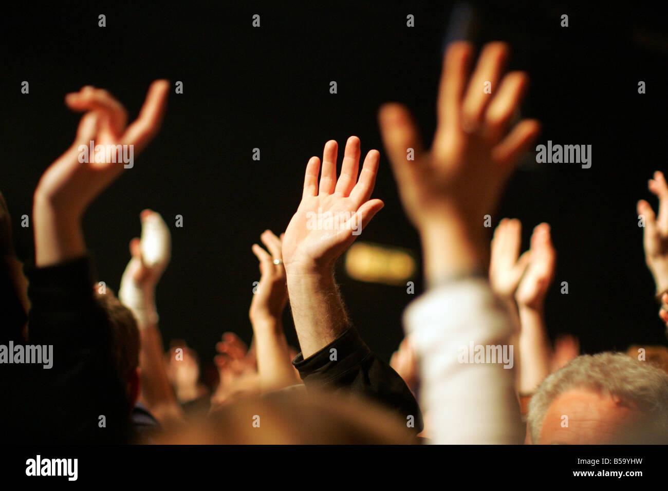 Fans levantando sus manos durante un concierto Foto de stock