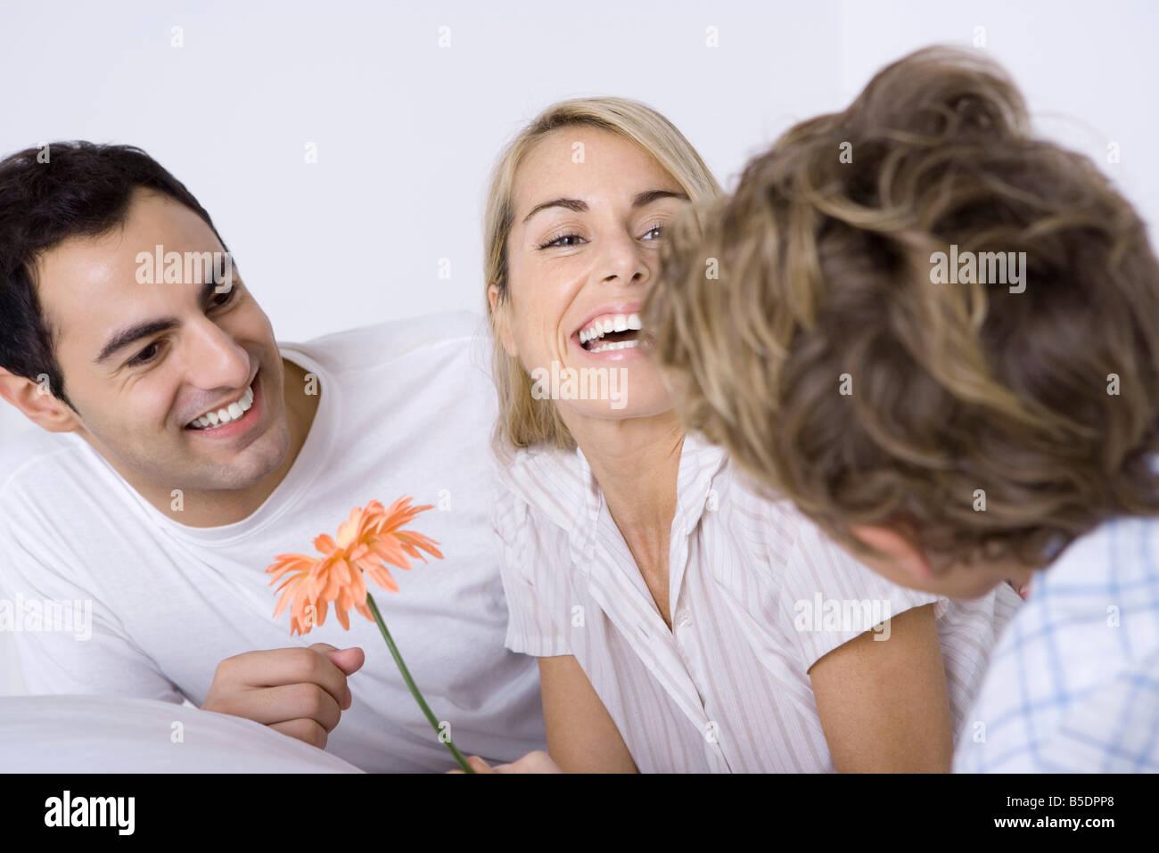 Mujer riendo con mi esposo e hijo, sosteniendo flor Imagen De Stock