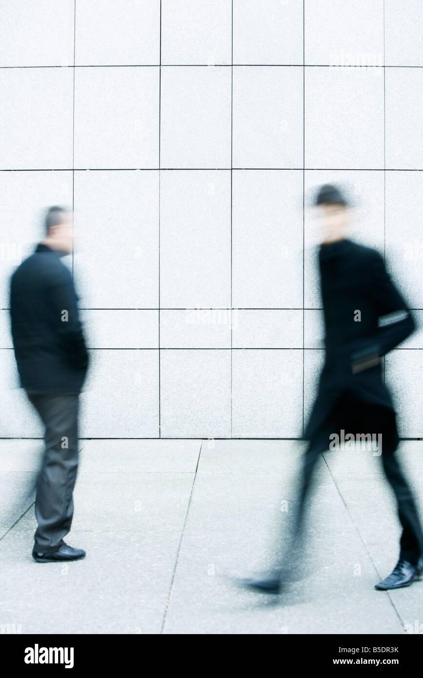Dos hombres pasar de uno a otro como caminan por la acera Foto de stock