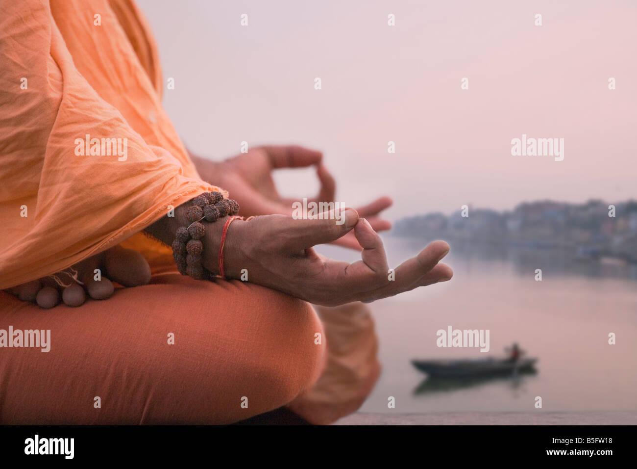 Hombre santo meditar en el banco del río de Ganges Varanasi India Imagen De Stock