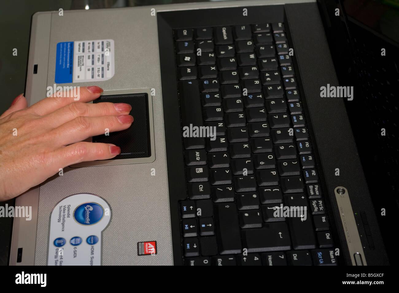 Persona Womans dedos mano usando el panel táctil de un ordenador portátil Imagen De Stock