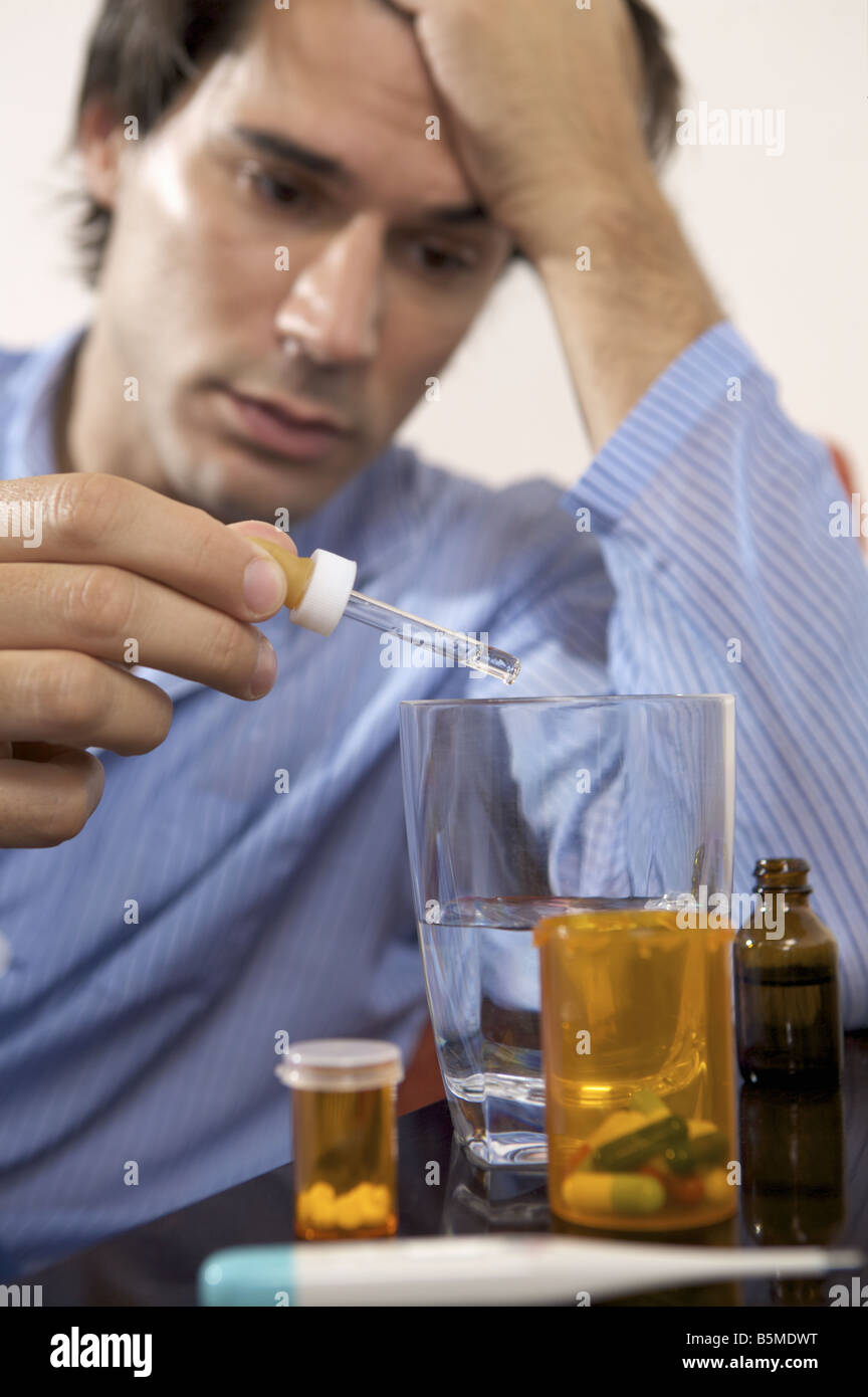 Un hombre poner gotas en un vaso Imagen De Stock