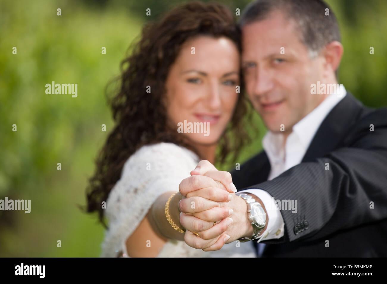 La novia y el novio las manos juntas, disparó al aire libre Imagen De Stock