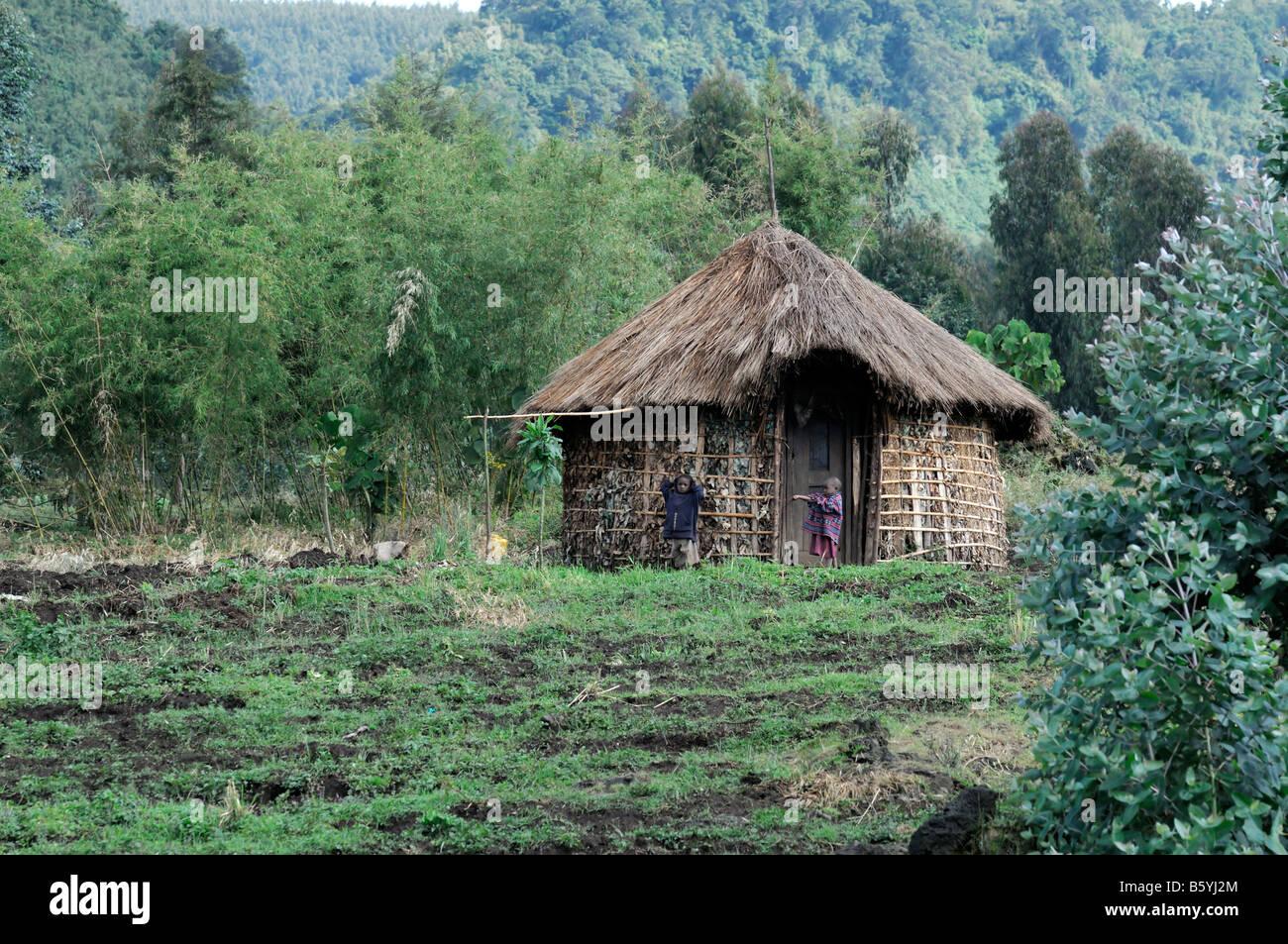 Dos niños fuera de una choza de barro tradicional típica casa simple pobreza pobres finca rural parque Imagen De Stock