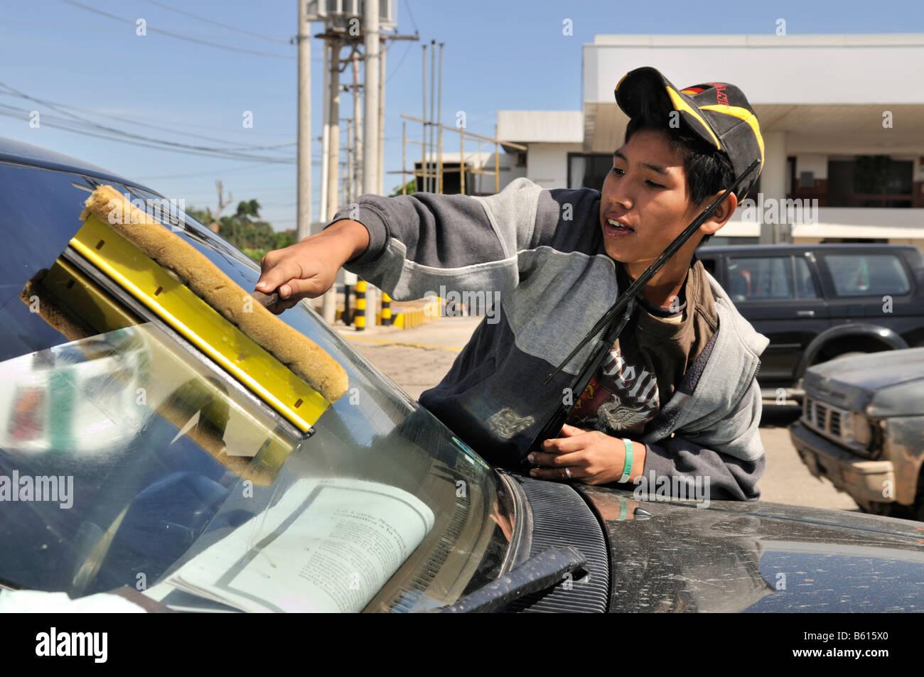 Varón de 15 años de limpieza de ventanas de autos en una intersección, Santa Cruz, Bolivia, América Imagen De Stock