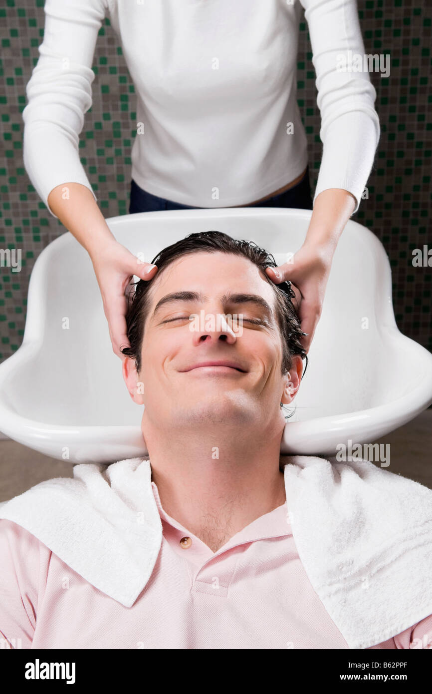 Mitad hombre adulto tener un lavar el cabello en la peluquería Foto de stock