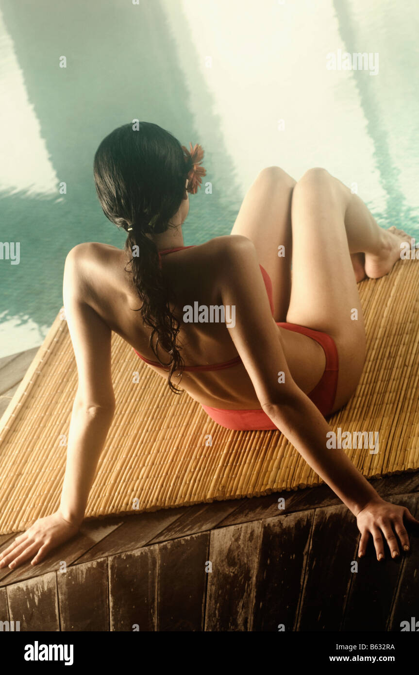 Un alto ángulo de vista de una joven mujer sentada al lado de la piscina Imagen De Stock