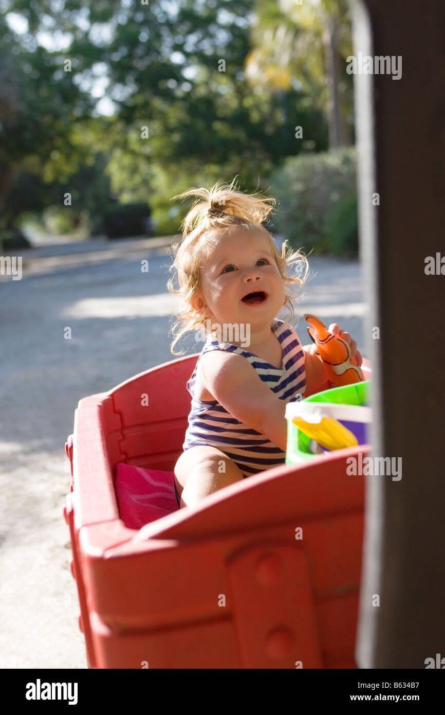 Nina Sentada Sobre Un Carro De Juguete Foto Imagen De Stock