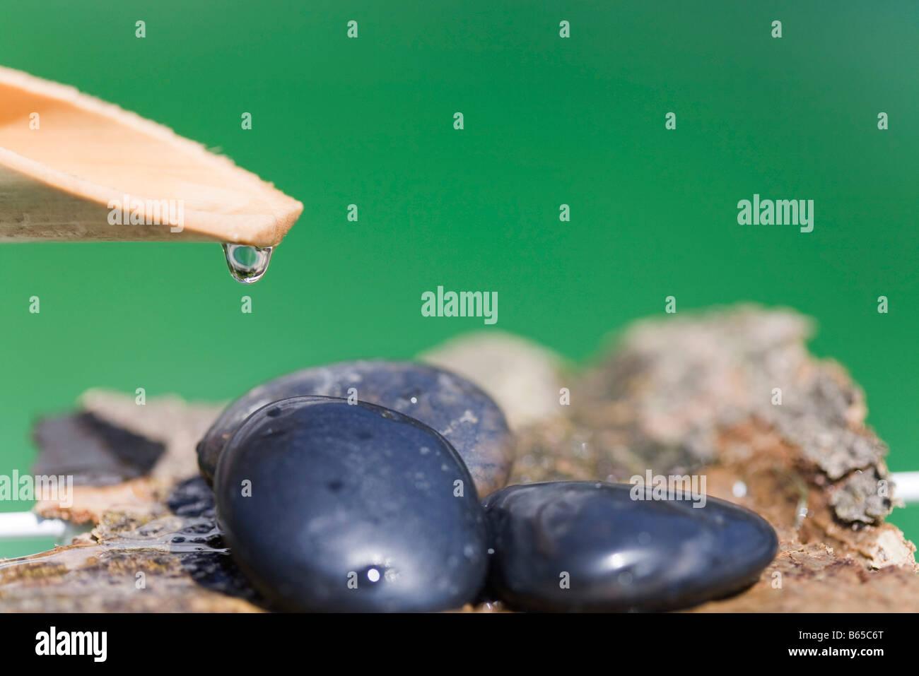 Gota de agua de madera colgando de descarga sobre el montón de piedras Imagen De Stock