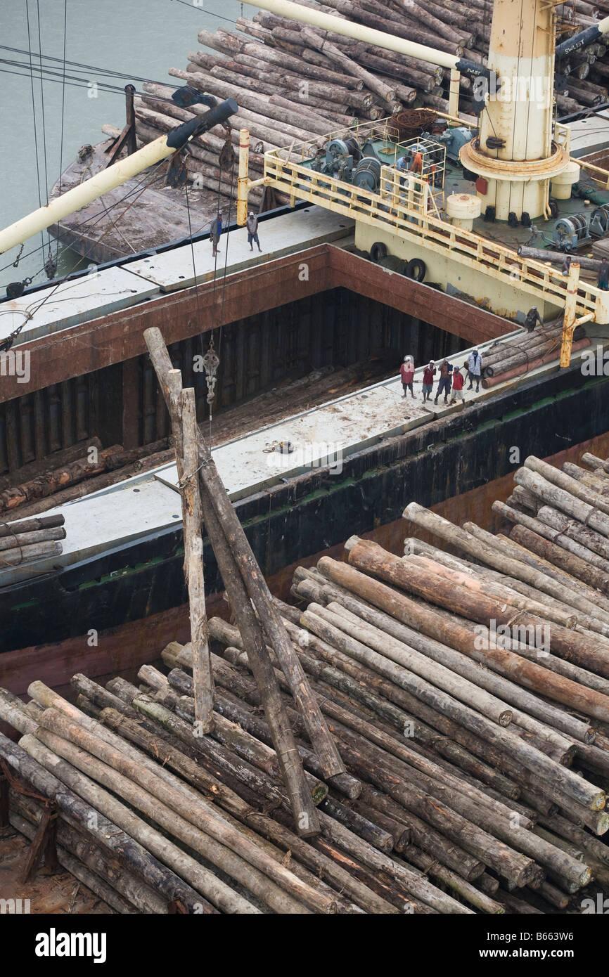 Carga de los árboles cortados ilegalmente desde barcazas en carguero en Paia Puerto, en Papua Nueva Guinea. Imagen De Stock