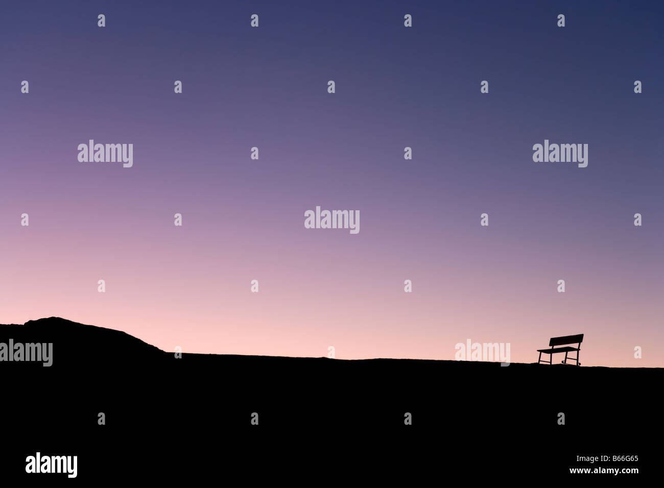 Silueta de banco solitario en el horizonte al atardecer, Zabriskie Point, el Parque Nacional Valle de la Muerte, Imagen De Stock