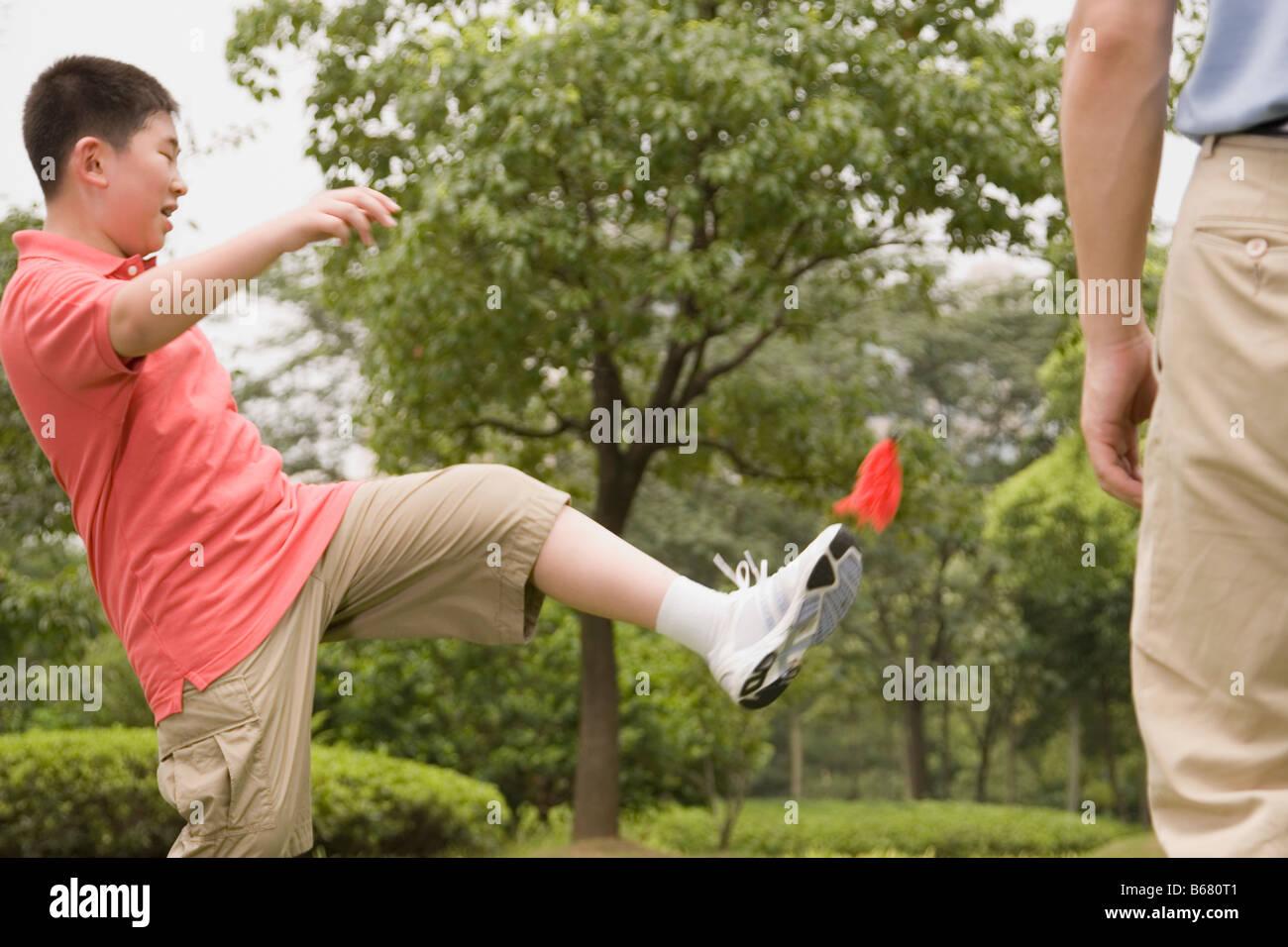 Muchacho jugando con un shuttlecock con su padre de pie delante de él Imagen De Stock