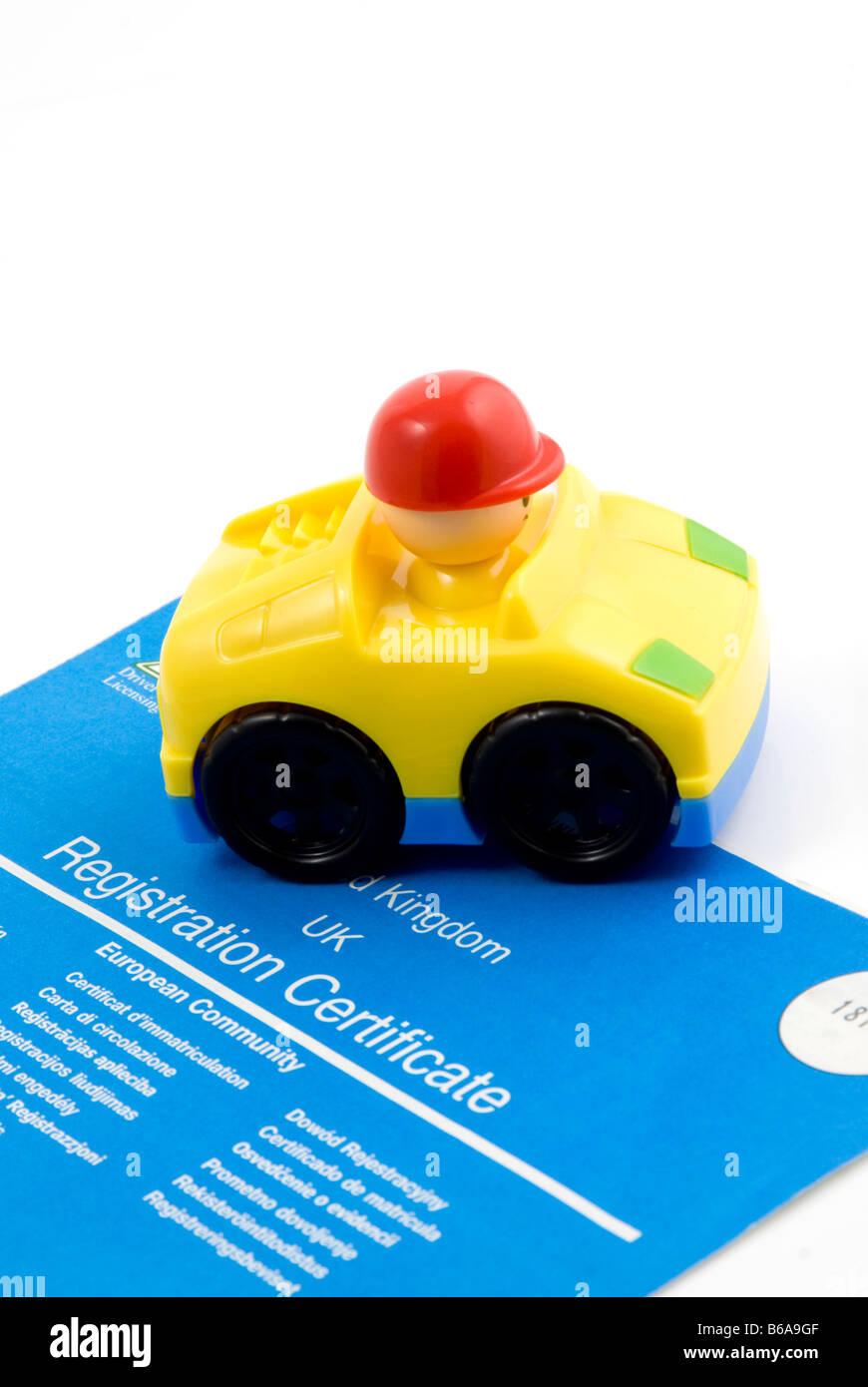 Coche de juguete con un documento de registro del coche Foto de stock