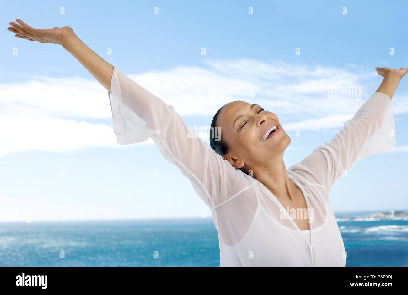 Mujer alegre y con los brazos extendidos al lado del mar. Imagen De Stock