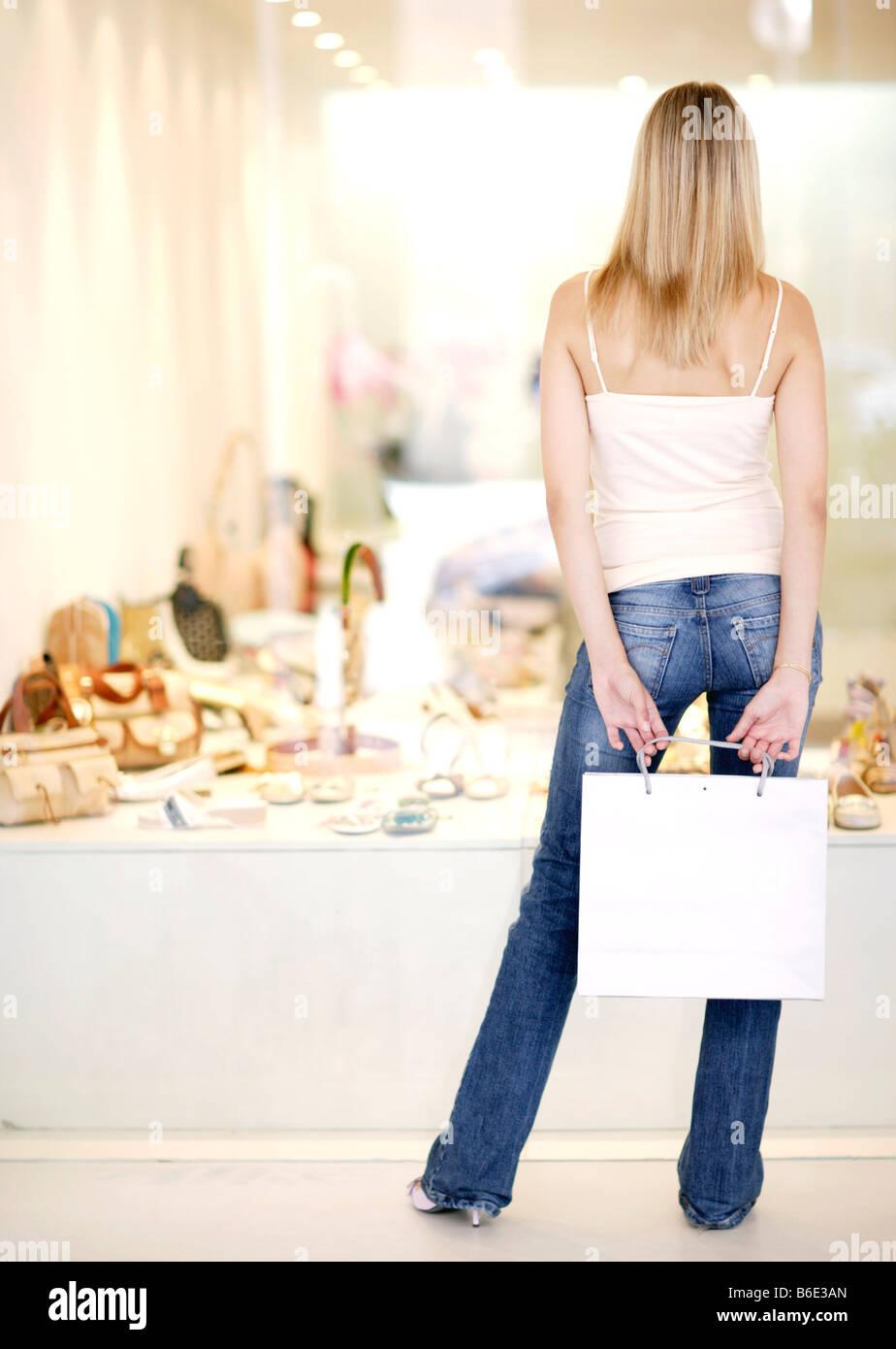 Mujer mirando zapatos en escaparate Foto de stock