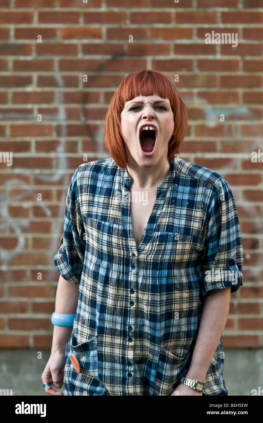 Pelo rojo enfurecido enojado joven Chica pelo rojo gritando y chillando gritando frenéticamente a la cámara Foto de stock