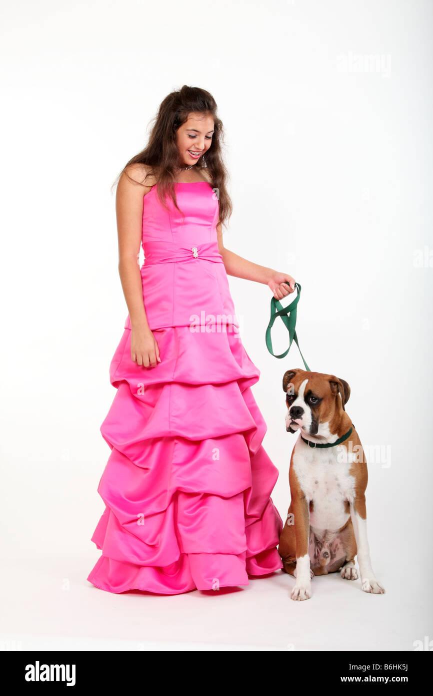 Una jovencita en un vestido de prom y un perro boxer con una correa ...