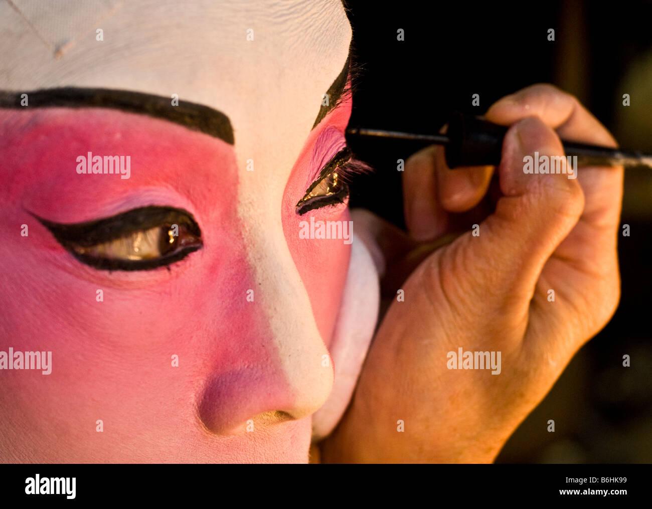 Una actriz hace de ella durante un ensayo de la ópera china. En este título, ella pinta cuidadosamente Imagen De Stock
