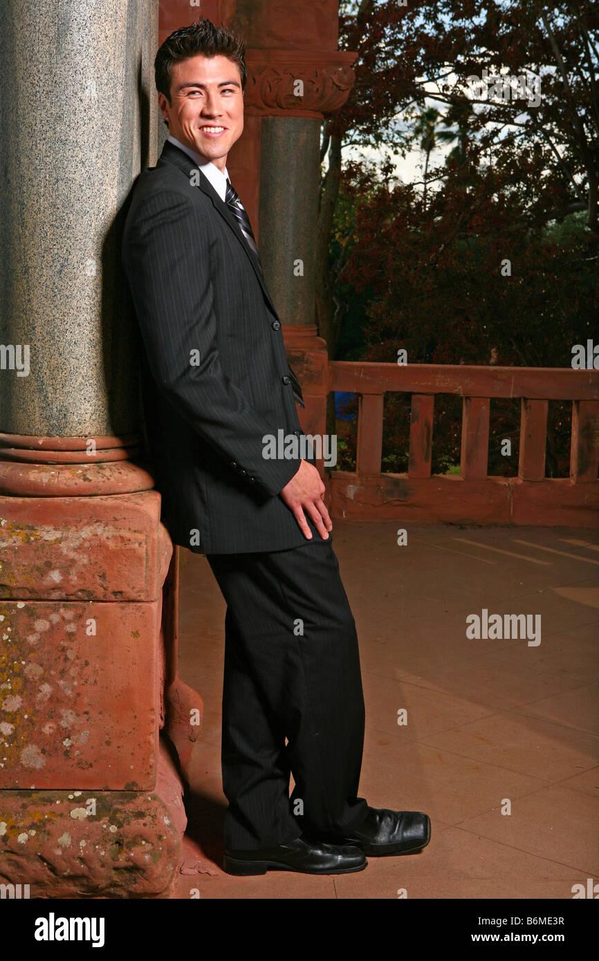 Apuesto hombre asiático sonriendo mientras está parado afuera Imagen De Stock