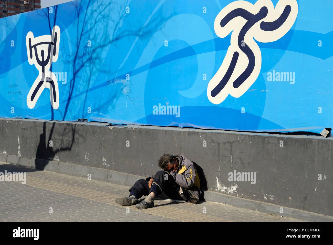 Un pobre hombre se sienta bajo un póster de los Juegos Olímpicos de Pekín 2008 en Beijing, China, Imagen De Stock