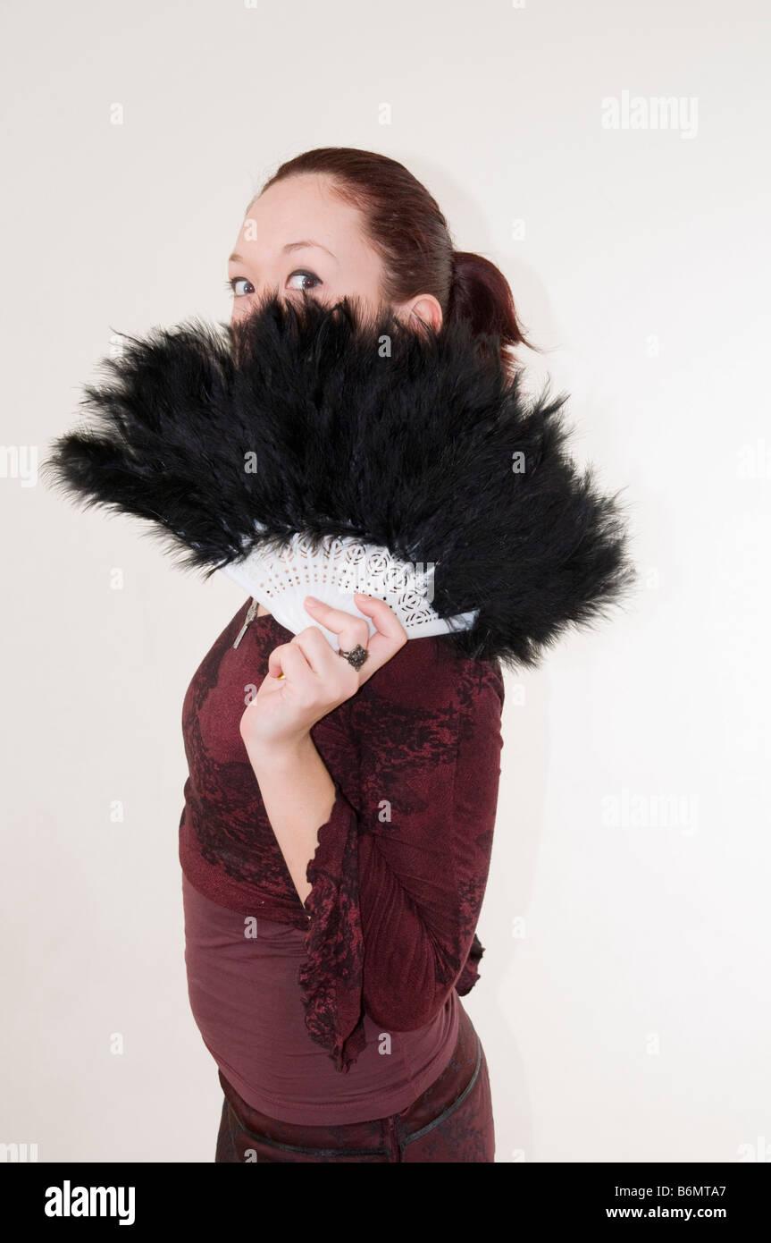 Joven adolescente gótico escondido detrás de un modelo de ventilador con plumas negras Release disponible Imagen De Stock