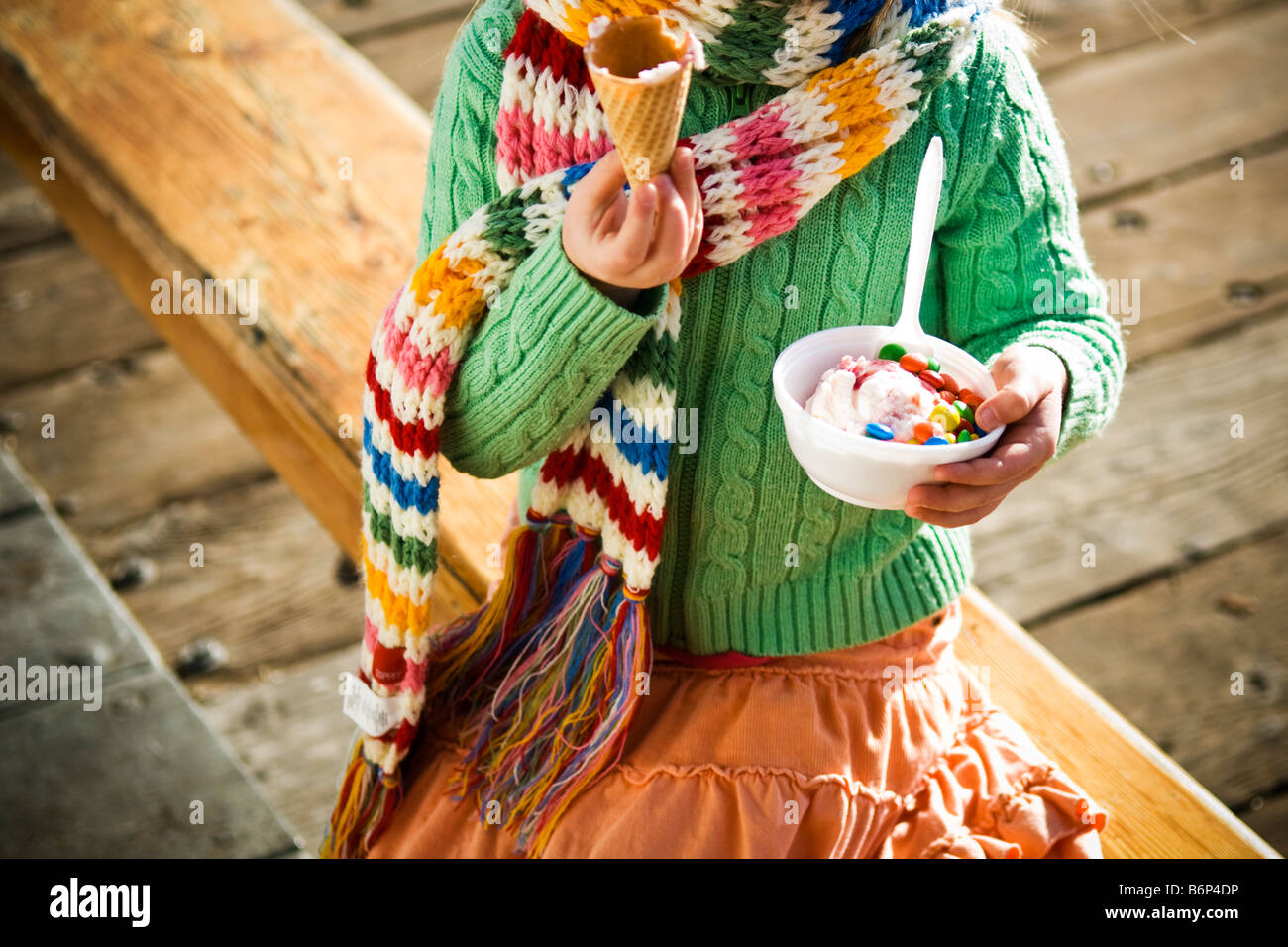 Una niña, de 4-5 años, disfruta de una taza de helado y m&M's en un día frío. Imagen De Stock