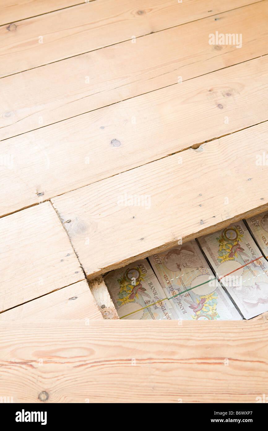 Dinero escondido bajo el suelo de madera Foto de stock