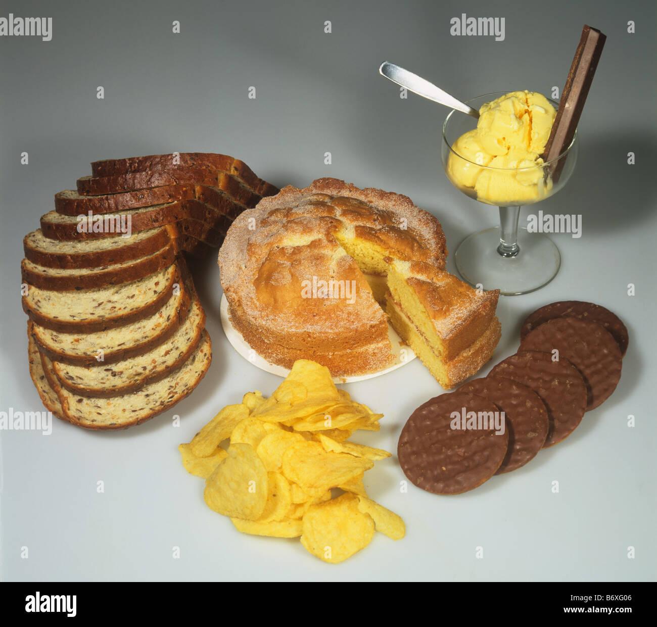 Los alimentos altos en carbohidratos de alta energía incluyendo la tarta galletas pan patatas fritas de chocolate Imagen De Stock
