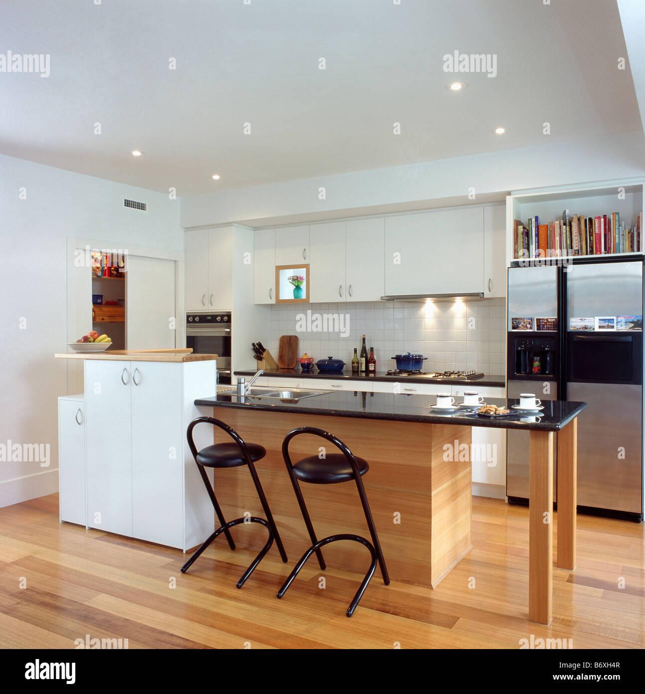 Los taburetes de metal negro en la barra de desayuno con base de madera y encimera de granito negro en la moderna cocina blanca con suelos de madera