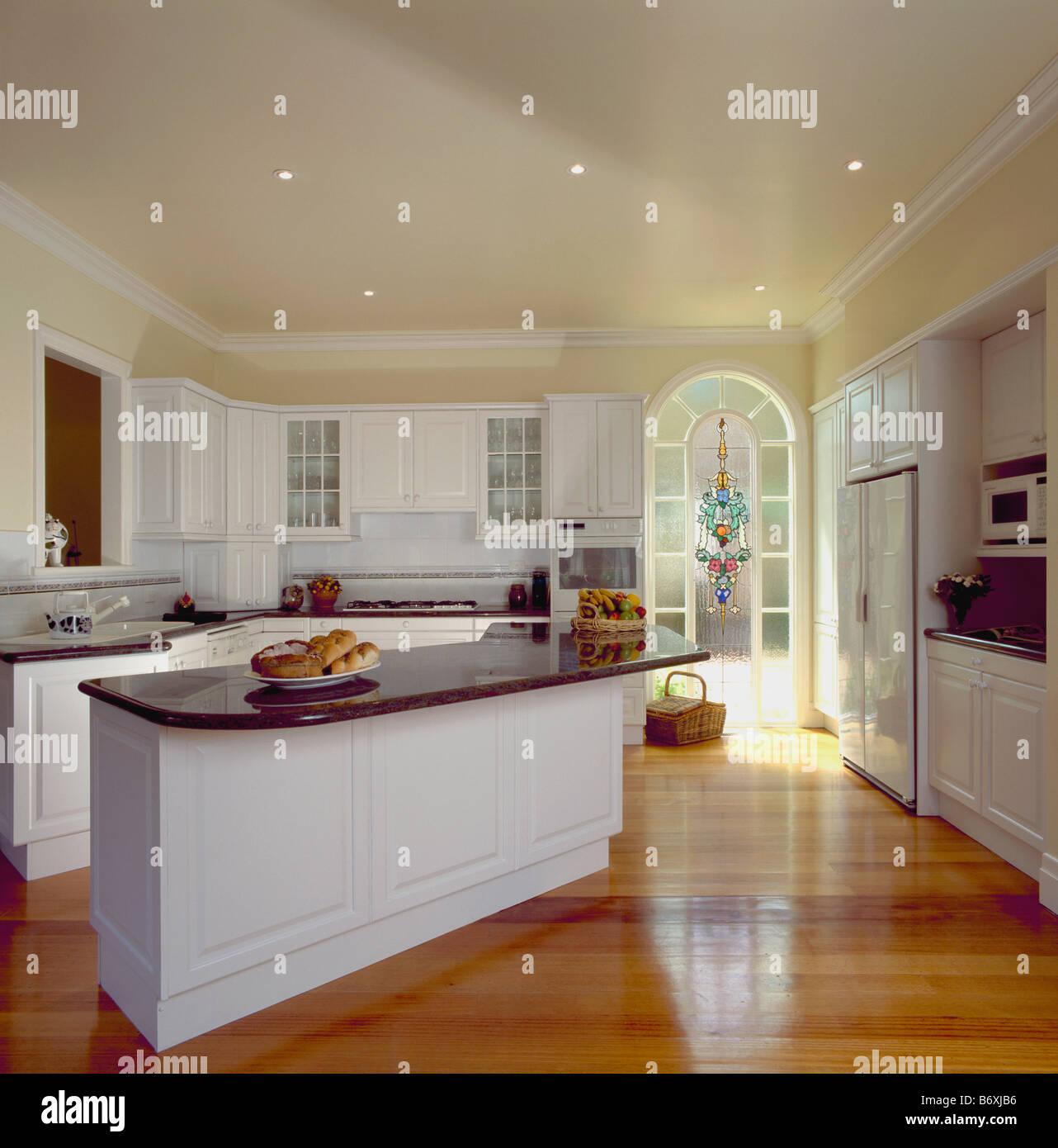 Suelos de madera lacada y la isla blanca unidad con encimera de granito negro en la moderna cocina blanca con arcos puerta acristalada