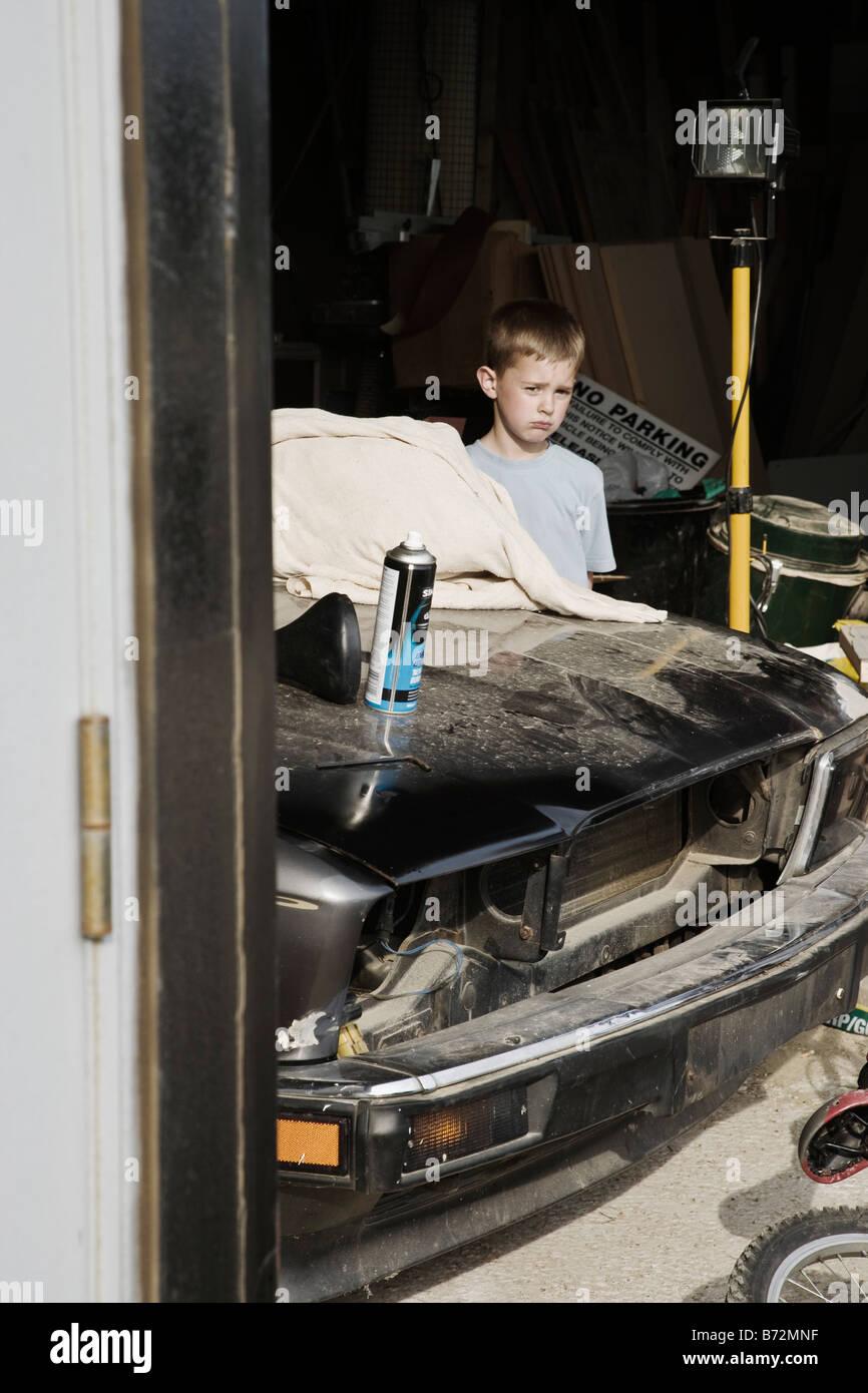 Niño de pie detrás de un coche en un garaje Imagen De Stock