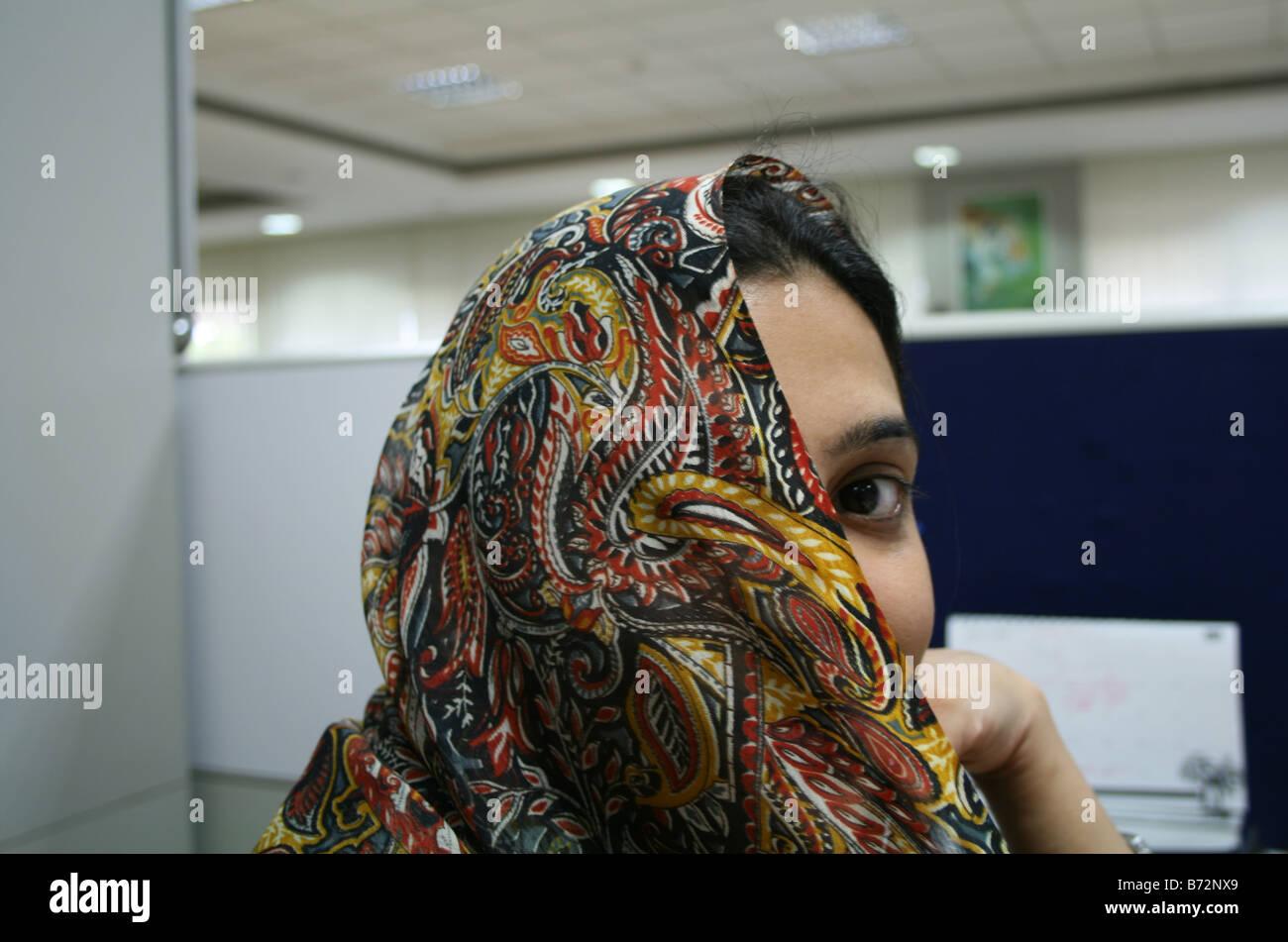 Cara de jóvenes musulmanes chica corporativa cubiertos parcialmente con un diseñador Parda trabajan en Imagen De Stock