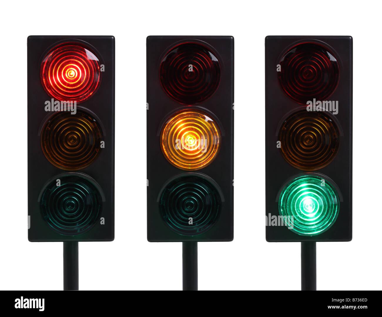 Tres semáforos en rojo amarillo y verde luces recortadas sobre fondo blanco. Imagen De Stock