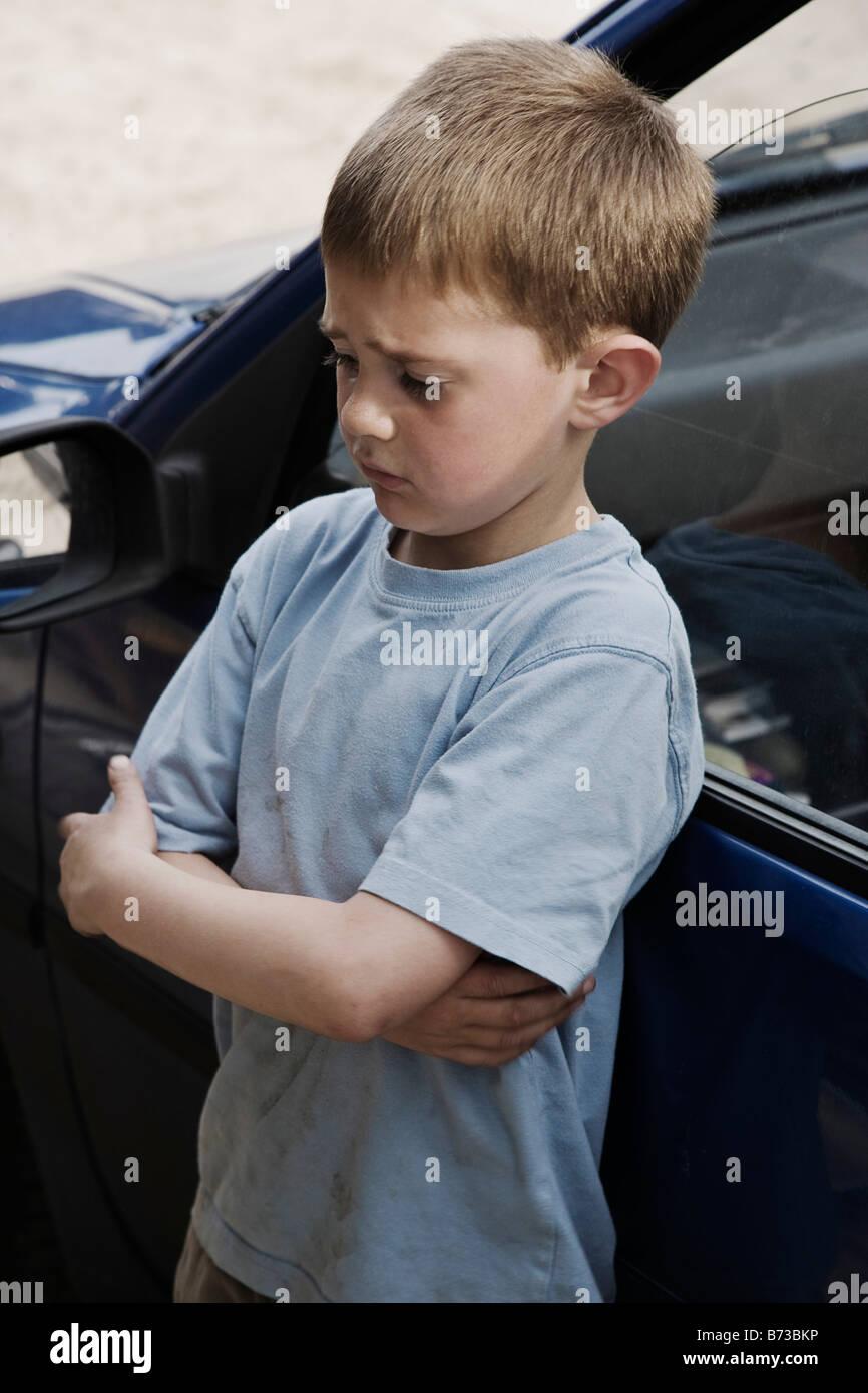 Boy refunfuñar, junto al coche Imagen De Stock